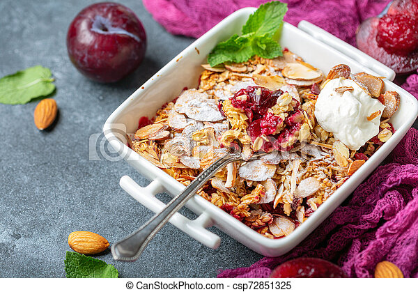 Red plum crumble with crunchy oatmeal and almond. - csp72851325