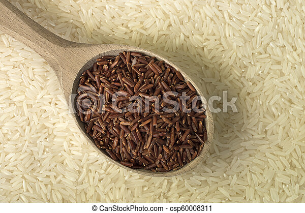 Red rice in a wooden spoon on white rice background - csp60008311