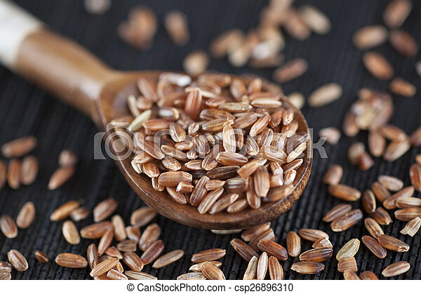Red rice in a wooden spoon - csp26896310
