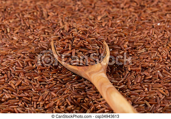 Red rice in a wooden spoon - csp34943613