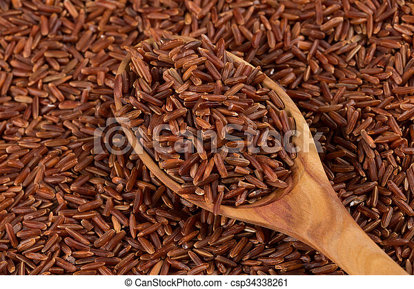 Red rice in a wooden spoon - csp34338261