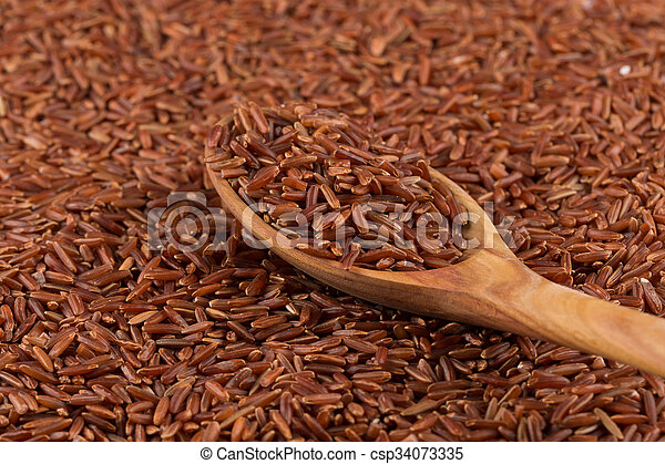 Red rice in a wooden spoon - csp34073335