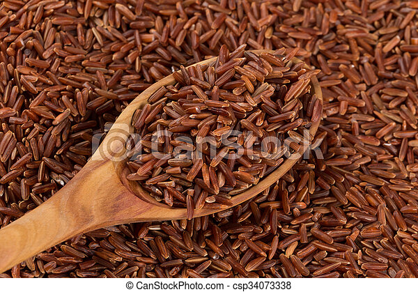Red rice in a wooden spoon - csp34073338