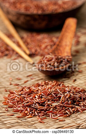 red rice on a straw background - csp39449130