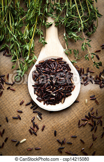 Red rice on wooden spoon - csp14215080