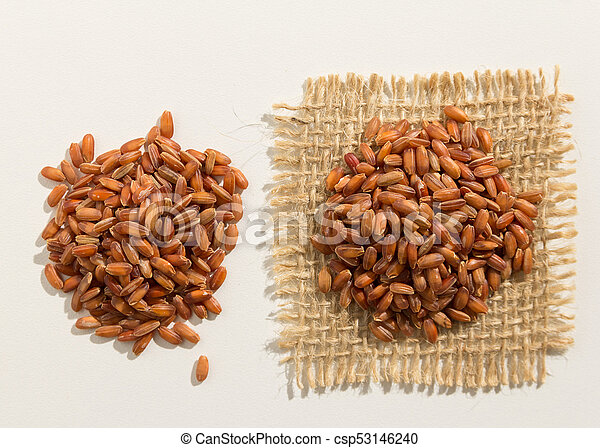 Red Rice seed. Close up of grains spreaded over white table. - csp53146240