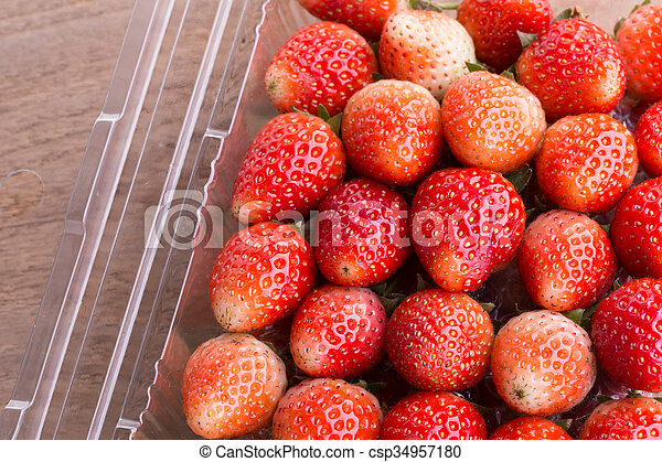 red ripe strawberry in plastic box of packaging - csp34957180