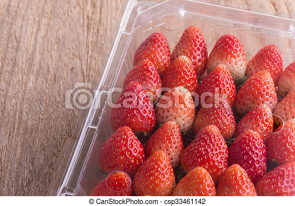 red ripe strawberry in plastic box of packaging - csp33461142