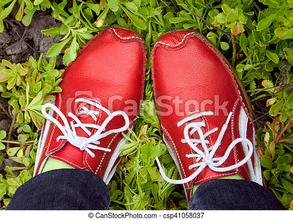 red running shoes on a grass - csp41058037