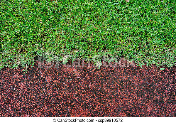 red running track and green grass in stadium - csp39910572