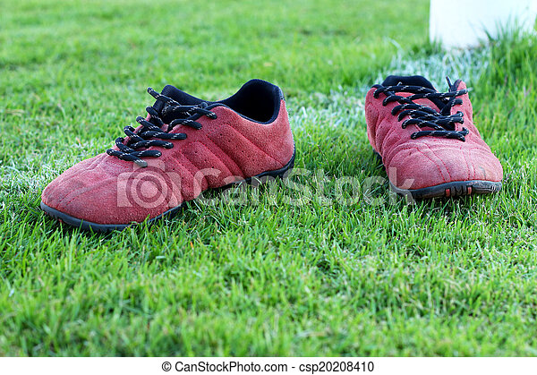 Red shoes green grass in a stadium. - csp20208410
