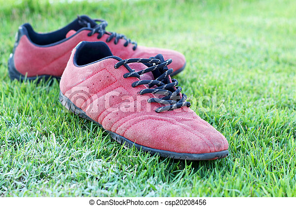 Red shoes green grass in a stadium. - csp20208456
