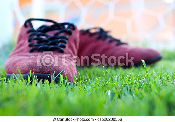 Red shoes green grass in a stadium. - csp20208556