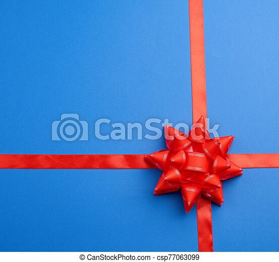 red silk ribbon crossed on a blue background in the middle of a red bow - csp77063099