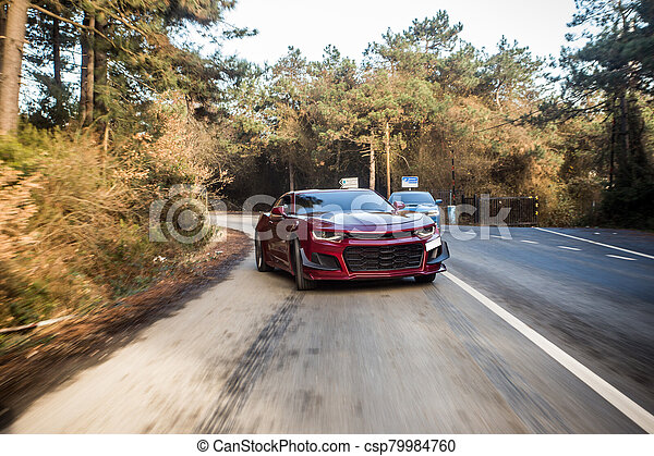 Red sport sedan on the forest road - csp79984760