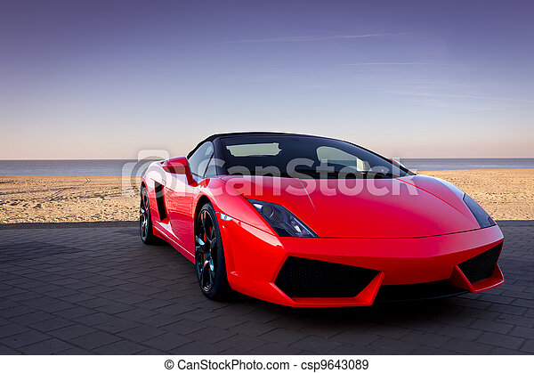 Red sports car at sunset beach - csp9643089
