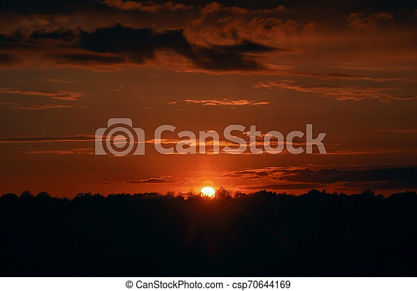 Red sunset. Beautiful evening sky. Orange rays of the sun - csp70644169