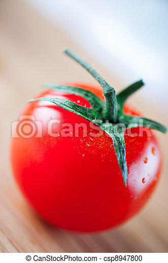 Red tomato on cutting board - csp8947800