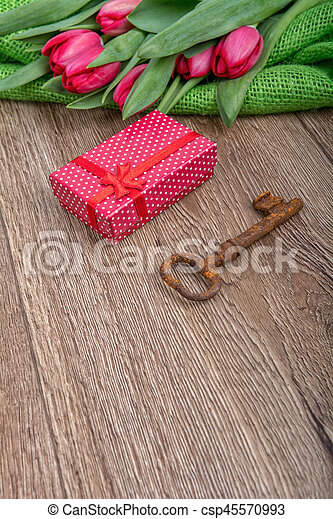 Red tulips, rusty key and gift on a wooden background - csp45570993