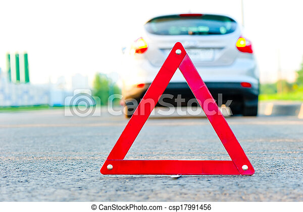 red warning triangle and a car with the emergency alarm - csp17991456