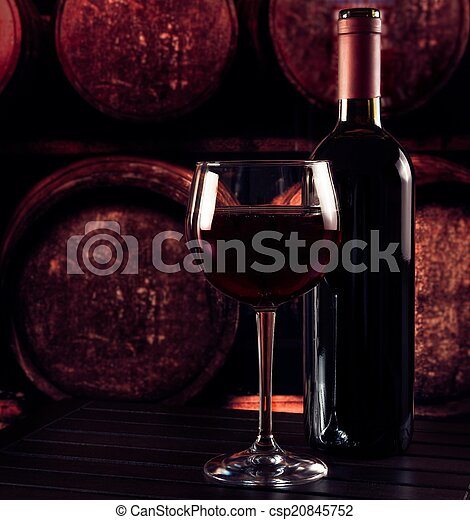 red wine glass near bottle on wood table and in old wine cellar background - csp20845752