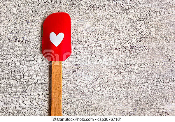 Red with heart kitchen spatula on wooden background - csp30767181