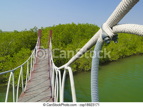 Red wooden bridge to a natural forest with blue sky, Thailand - csp18923171