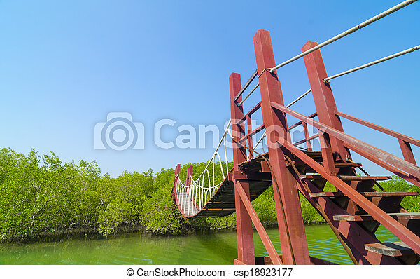Red wooden bridge to a natural forest with blue sky, Thailand - csp18923177