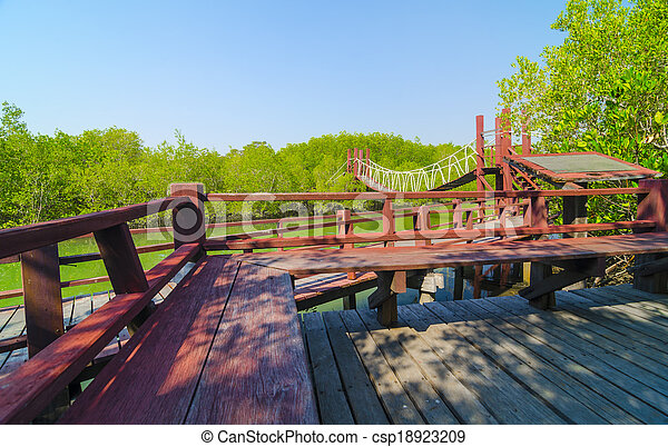 Red wooden bridge to a natural forest with blue sky, Thailand - csp18923209