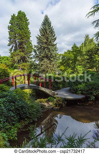 Red wooden Japanese foot bridge add theme to garden - csp21732417