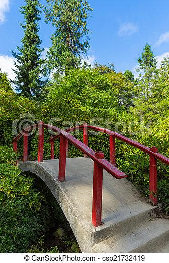 Red wooden Japanese foot bridge add theme to garden - csp21732419