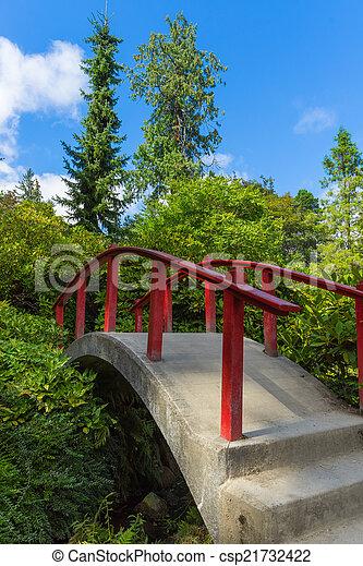 Red wooden Japanese foot bridge add theme to garden - csp21732422