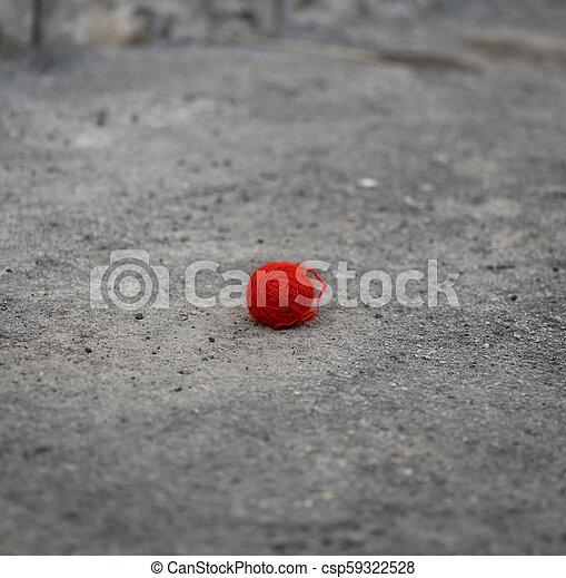 red woolen ball lies on the gray asphalt - csp59322528