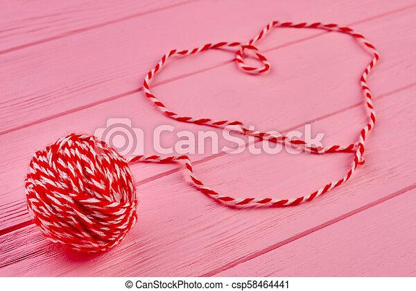 Red woolen ball of yarn. - csp58464441