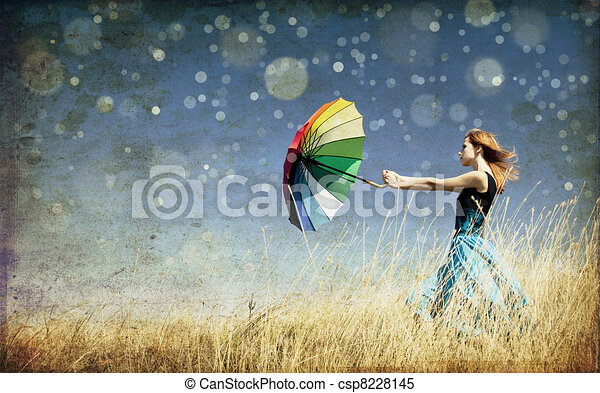 Redhead girl with umbrella at windy grass meadow. Photo in old color image style. - csp8228145