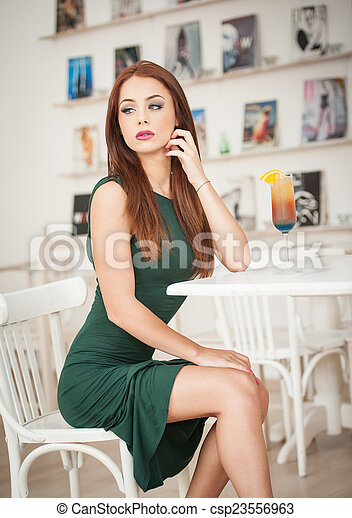 Redhead in restaurant with juice - csp23556963
