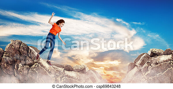 Redhead woman falling down between hills on cliff. - csp69843248