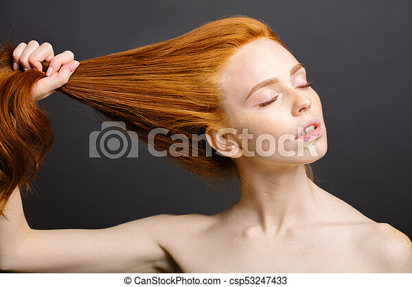 redhead woman holding her healthy and shiny hair, studio grey - csp53247433
