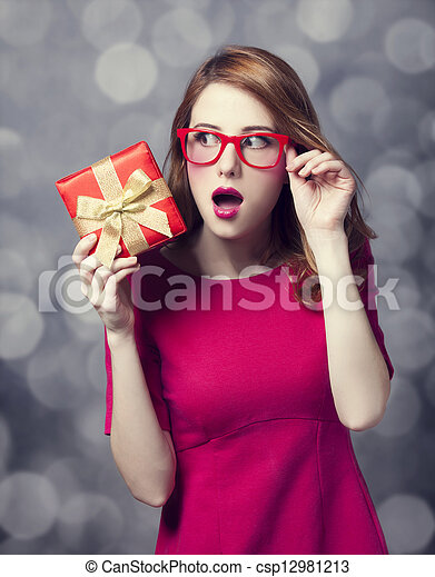 Redhead woman in dress with present box. Bokeh. - csp12981213