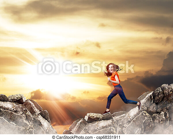 Redhead woman jumps over cliff on blue sky background. - csp68331911