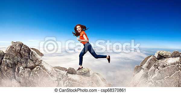 Redhead woman jumps over cliff on blue sky background. - csp68370861