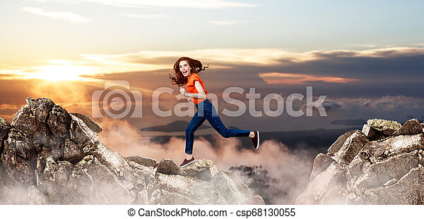 Redhead woman jumps over cliff on blue sky background. - csp68130055