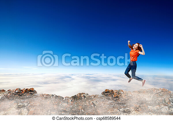 Redhead woman jumps over cliff on blue sky background. - csp68589544
