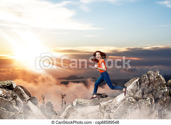 Redhead woman jumps over cliff on blue sky background. - csp68589548