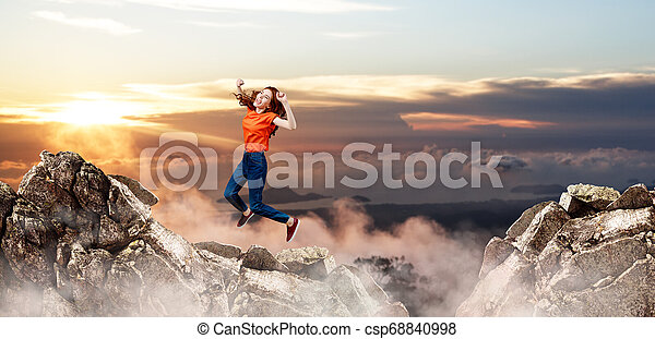 Redhead woman jumps over cliff on blue sky background. - csp68840998
