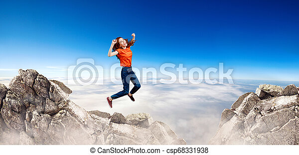 Redhead woman jumps over cliff on blue sky background. - csp68331938