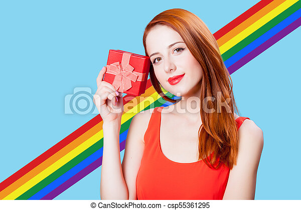 Redhead woman with gif box on blue background - csp55361295