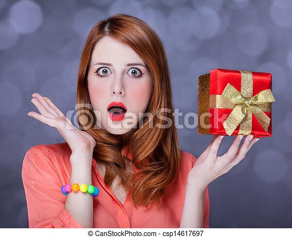 Redhead woman with present box. Bokeh. - csp14617697