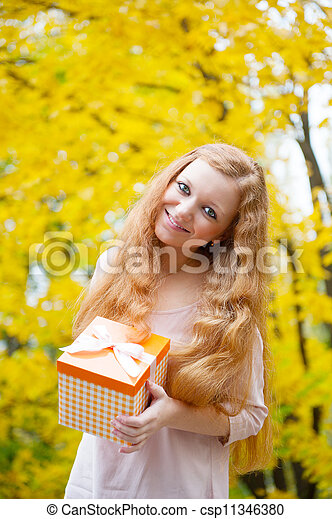 Redhead woman with present box in autumn park - csp11346380