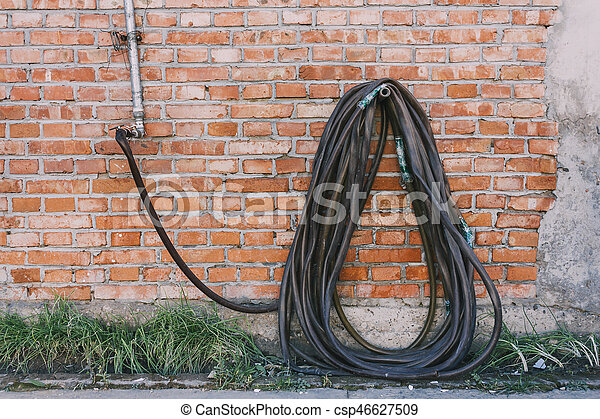 Reel of black hose pipe and spraying head on the red texture Brick wall - csp46627509